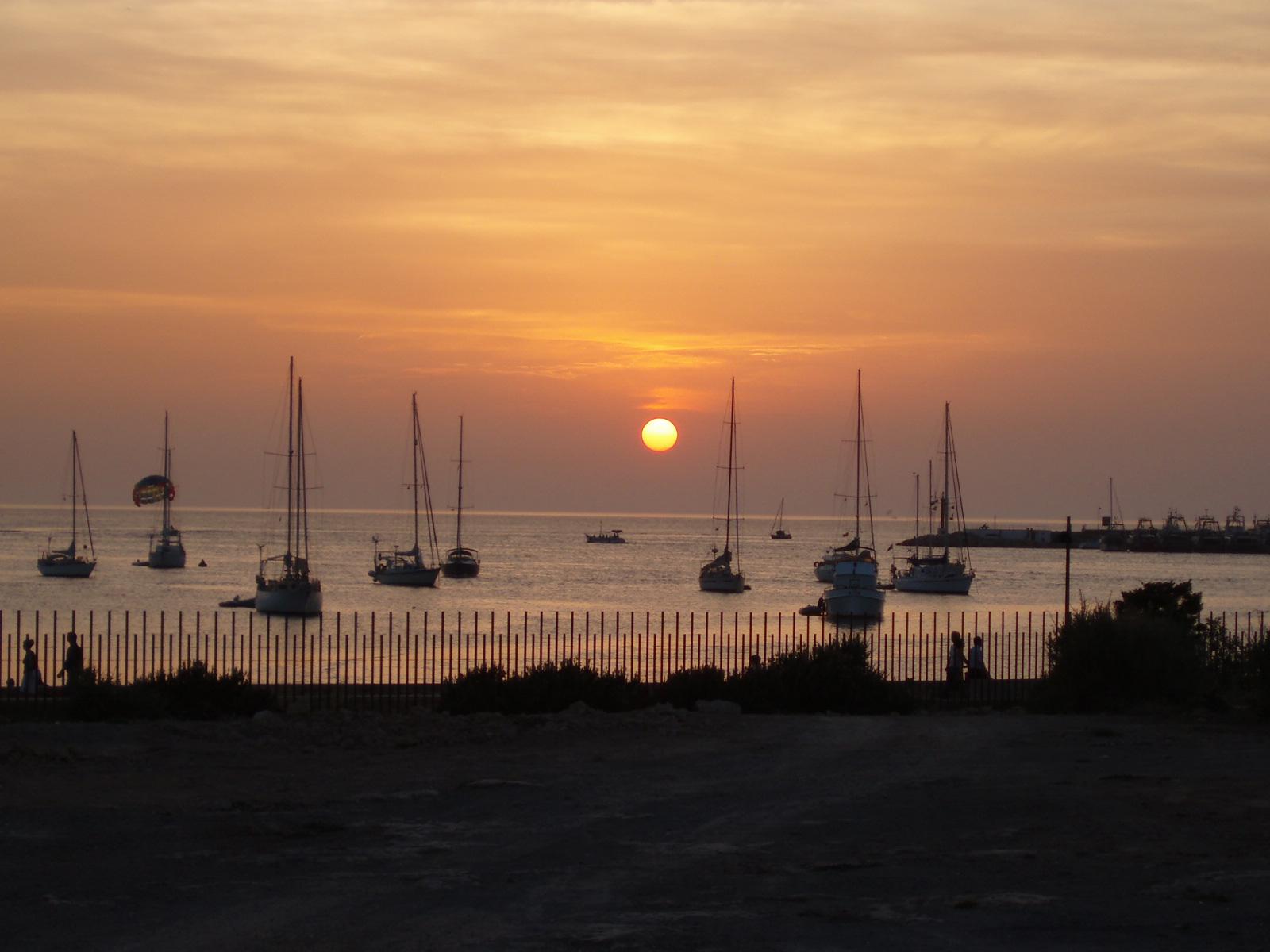 Foto playa San Antonio / Es Regueró. Velas y parasailing atardecer