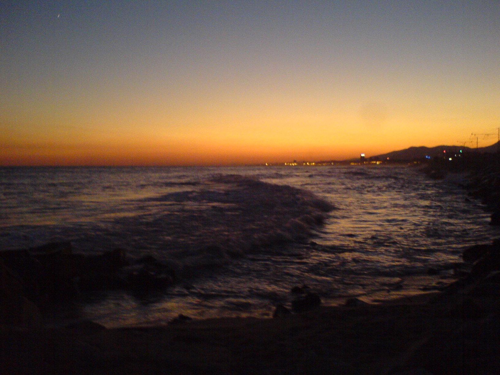 Foto playa Les Barques / Las Barcas. El mar i Mataró de fons, posta de sol