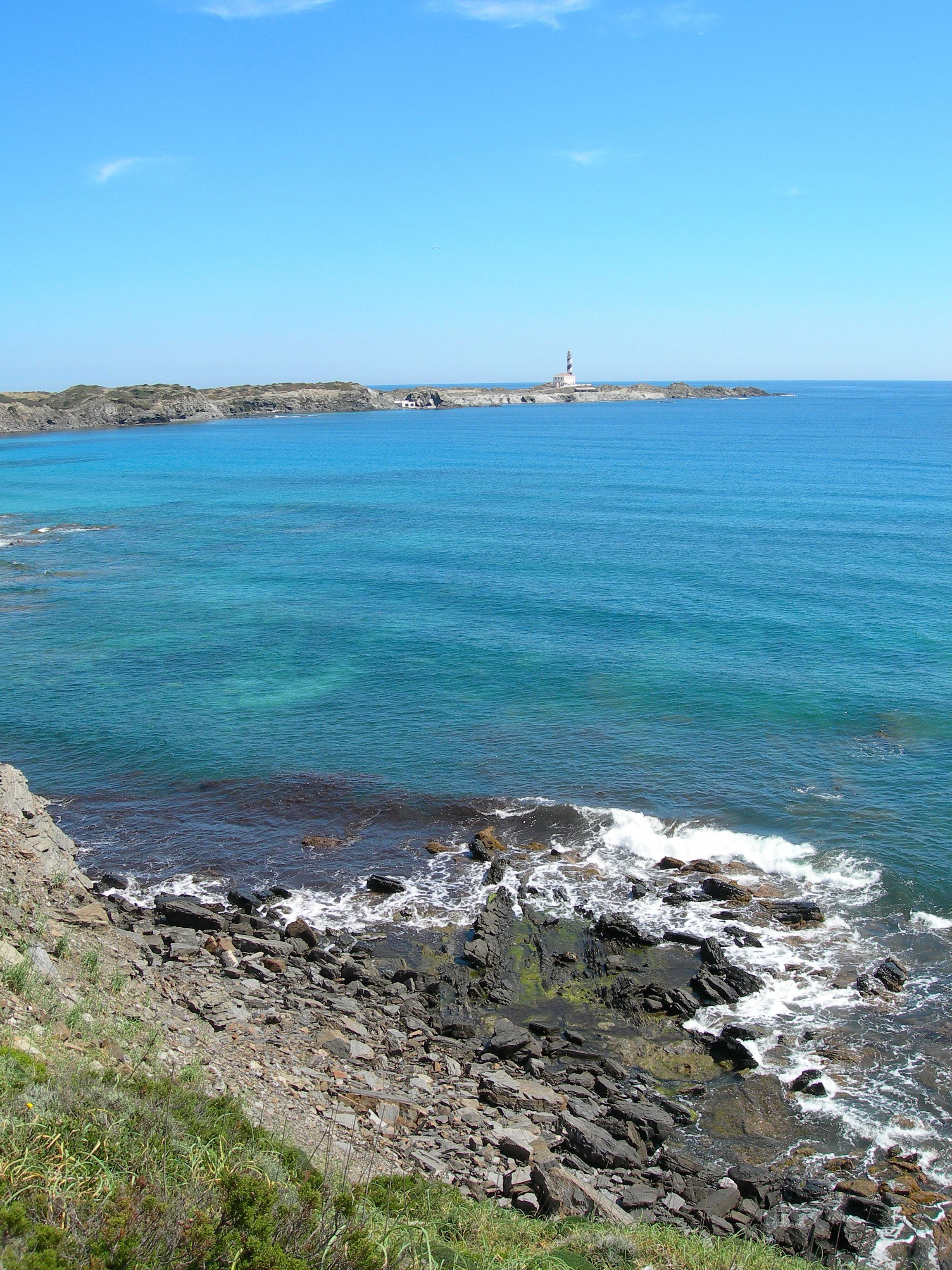 Foto playa Cala Morella Nou. El cabo y faro de Favaritx, desde el Camí de Cavalls, muy cerca de Cala Tortuga. Costa E. de Menorca.-